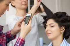 Nehmendes Vorlagenfoto des Salons auf Smartphone der Schönheitsfrau beim Make-up an setzen und Herstellung von hairdro Stockfotos