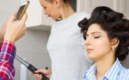 Nehmendes Vorlagenfoto des Salons auf Smartphone der Schönheitsfrau beim Make-up an setzen und Herstellung von hairdro Lizenzfreies Stockfoto