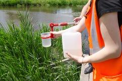 Nehmenproben des Wassers für Laborversuche Das Konzept - Analyse der Wasserreinheit, Umwelt, Ökologie lizenzfreie stockbilder