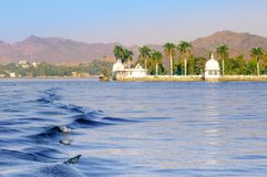 Nehru island on fateh sagar lake Udaipur with hills and water wa. Nehru island on fateh sagar lake in Udaipur india. The white domes and trees of the island are Royalty Free Stock Images