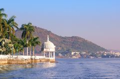 Nehru island on fateh sagar lake Udaipur with hills and water wa. Nehru island on fateh sagar lake in Udaipur india. The white domes and trees of the island are Stock Image