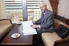 Uomo d'affari senior che supera le carte Fotografia Stock