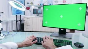 Nei tipi moderni del professionista del laboratorio sul computer verde dello schermo stock footage