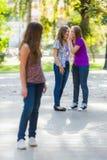 Neidische Mädchen, die hinter ihrer Freundin sprechen Lizenzfreie Stockfotos