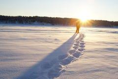 Neige chaussant dans le coucher du soleil Photographie stock libre de droits