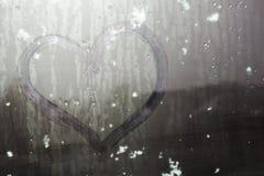 Neige collante sur un coeur tiré par la main sur le verre en sueur Images libres de droits