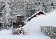 Neige de bâti de tracteur contre au-dessus d'une barrière Photographie stock