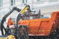 Neige de charge d'excavatrice dans le camion rues de dégagement de la neige b photo libre de droits