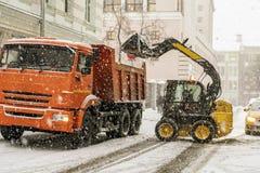 Neige de charge d'excavatrice dans le camion rues de dégagement de la neige b image libre de droits