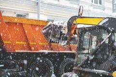 Neige de charge d'excavatrice dans le camion rues de dégagement de la neige b photo stock