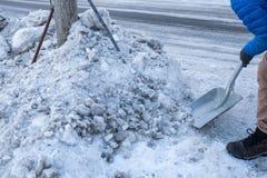 Neige de dégagement d'homme avec la pelle sur le bord de la route image libre de droits