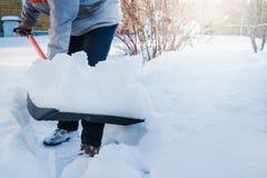 Neige de dégagement d'homme par la pelle après des chutes de neige outdoors photographie stock