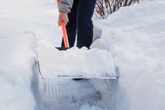 Neige de dégagement d'homme par la pelle après des chutes de neige outdoors photos libres de droits