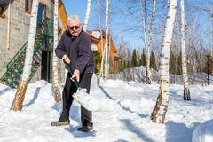Neige de lancement d'homme supérieur avec la pelle de la cour privée de maison en hiver le jour ensoleillé lumineux Personne âgée photos stock