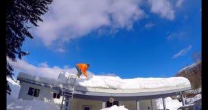 Neige de nettoyage d'homme du toit 4k de maison banque de vidéos