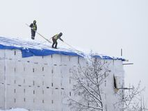 Neige de nettoyage sur le toit à Moscou photos stock