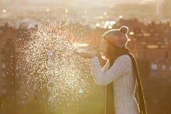Neige de soufflement de femme avec le coucher du soleil incroyable dans Noël Photo stock