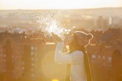 Neige de soufflement de femme avec le coucher du soleil incroyable dans Noël Image libre de droits