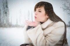 Neige de soufflement de fille de l'hiver image stock