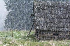 Neige en retard lourde au-dessus d'une carlingue en bois dans les montagnes carpathiennes Images stock