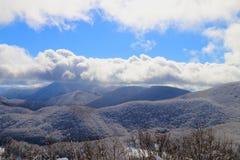 Neige et ciel bleu avec les nuages et le bâton Image libre de droits