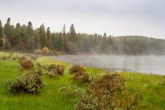 Neige légère au-dessus d'un lac de cuisson à la vapeur mountain Images stock