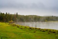 Neige légère au-dessus d'un lac de cuisson à la vapeur mountain Photographie stock