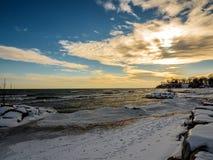 Neige le lac Ontario d'hiver congelée par coucher du soleil Images stock