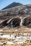 Neige noire de witn de montagne et ci-dessous avec des touristes au sol avec l'herbe brune, la neige et l'étang congelé en hiver  Photo stock
