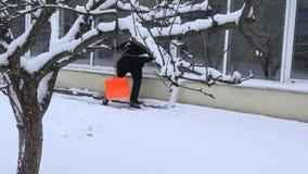 Neige propre d'homme de gardien de Chambre de sentier piéton près de maison dans l'horaire d'hiver 4K banque de vidéos