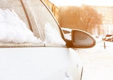 Neige sur des voitures après des chutes de neige Scène urbaine d'hiver avec la fusée du soleil images libres de droits