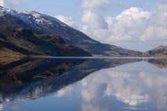 Neige sur la colline dans la réflexion de lac Image stock