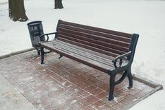 Neige sur le banc en parc de l'hiver Photo libre de droits