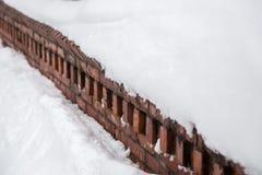 Neige sur le mur de briques rouge Photos libres de droits