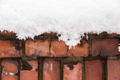 Neige sur le vieux mur de briques rouge Photographie stock