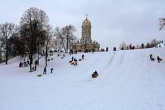 Neige-tuyauterie de personnes en parc d'hiver dans le village de Dubrovitsy près de Podolsk image libre de droits