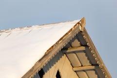 Neigez sur le toit de la maison au coucher du soleil photos libres de droits