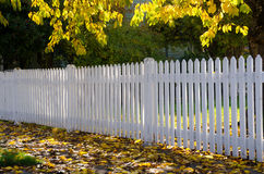 Neighborhood fence. Dappled sun caresses a simple white picket fence running along a sidewalk strewn with gold and brown fall leaves. A symbol of the simplicity Stock Photography