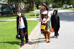 Neighborhood Kids Trick or Treat. Children in Halloween costumes trick or treating in their neighborhood. They look disappointed not to have gotten more candy royalty free stock photos