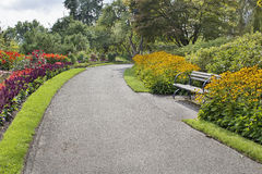 Neighborhood Parks Flowers Lined Path. Neighborhood Public Parks Lined with Colorful Flowers Trees and Shrubs with Park Bench Stock Image