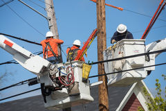 Neighborhood powerline workers. Three lineman in buckets hover hign in the air over houses as they work to replace a power pole stock photo