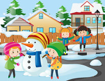 Neighborhood scene with kids playing with snowman Royalty Free Stock Image