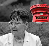 Neighbourhood watch. Photo of someone hiding in a red mail box keeping an eye on a vulnerable pensioner Stock Photo
