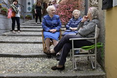 Neighbours and friends. Three women having a chat seated outside in Bellagio,Lake Como,Italy Royalty Free Stock Photo