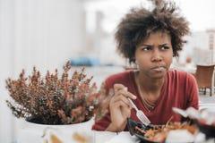 Neigung-Schiebeporträt des nachdenklichen brasilianischen Mädchens, das in Straße c isst lizenzfreie stockfotografie