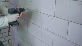 Neigung schoss oben von den ErbauerBohrlöchern in der Blockwand mit elektrischer Bohrmaschine stock video footage