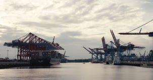 Neigung vom Himmel unten zum breiten Schuss des großen Containerschiffs, der kleineren Frachtschiffe und der Portalkräne im Hafen stock video