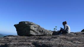 Neigungs-unten Frau sitzt auf Rock und Spielen am Telefon weit stock video footage