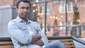 Nein, den jungen afrikanischen Mann zurückweisend, der auf Bank sitzt stock footage