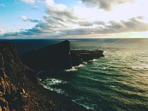 Neist Point lighthouse on rocky cliff above wavy sea. Blue evening sea and sharp cliffs,. Isle of Skye, Scotland Stock Photo